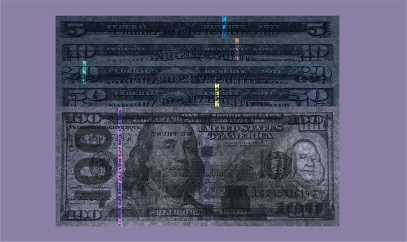 $5, $10, $20, $50, and $100 bills under UV light showing brilliant strips of special thread.