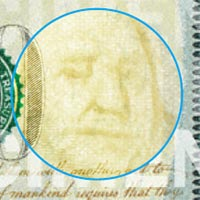 Close up of watermark of Benjamin Franklin's face on the 2013 $100 bill.