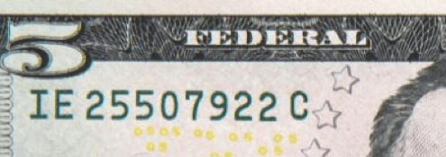 Enlarged excerpt of a $5 note showing the serial number