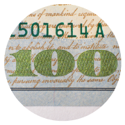 The number 100 in green in the bottom right corner of a $100 bill.